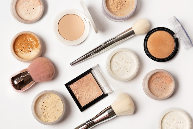 Mise à plat de surligneurs de maquillage, de poudre et de pinceaux sur fond blanc