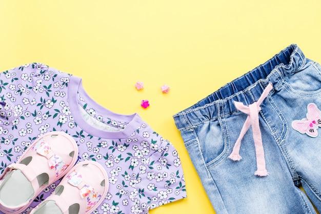 Mise à plat avec t-shirt à fleurs, jeans, sandales sur jaune