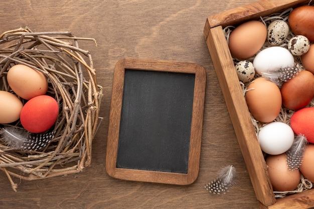 Mise à plat de tableau noir avec à côté avec des oeufs pour pâques