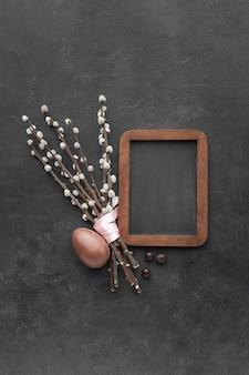 Mise à plat de tableau noir avec oeuf de pâques au chocolat et fleurs