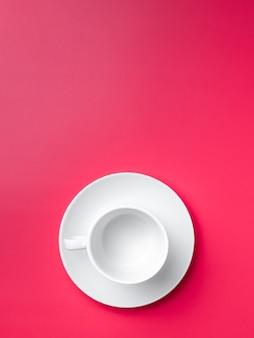 Mise à plat. tasse blanche vide sur une soucoupe sur fond rose. copiez l'espace.