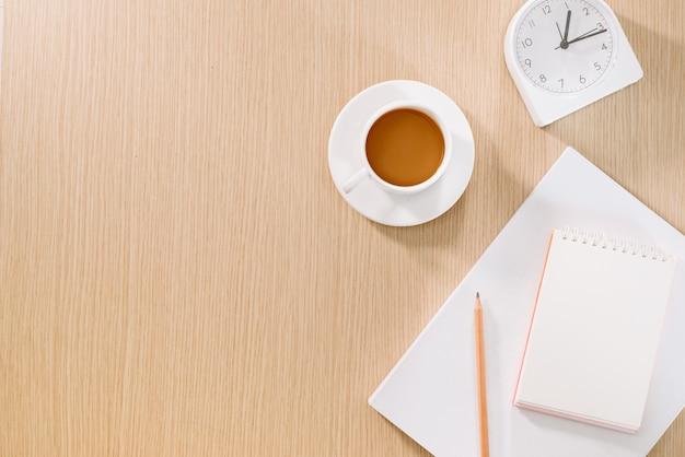 Mise à plat d'une tasse à café, d'une horloge, d'un crayon et d'un cahier.