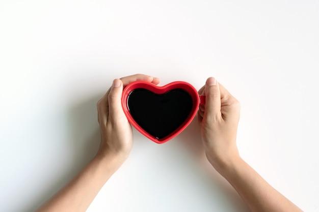 Mise à plat d'une tasse de café noir en forme de coeur entre les mains des femmes sur un bureau blanc avec espace de copie.