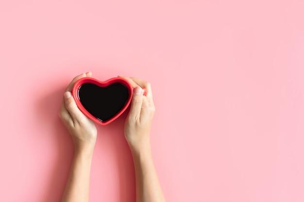 Mise à plat d'une tasse de café noir en forme de coeur entre les mains des femmes sur rose pastel