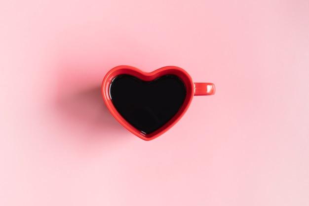 Mise à plat d'une tasse de café noir en forme de coeur sur fond rose avec espace de copie.