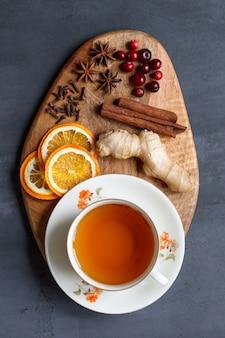 Mise à plat d'une tasse de thé, gingembre, oranges séchées, anis, bâtons de cannelle, clous de girofle, canneberges