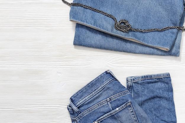 Mise à plat de tenues de mode décontractée pour femmes sur fond en bois blanc, jean bleu et petit sac en denim. vêtements féminins avec espace copie.