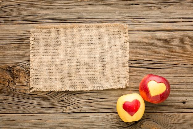 Mise à plat de tissu et de pommes avec des formes de coeur de fruits