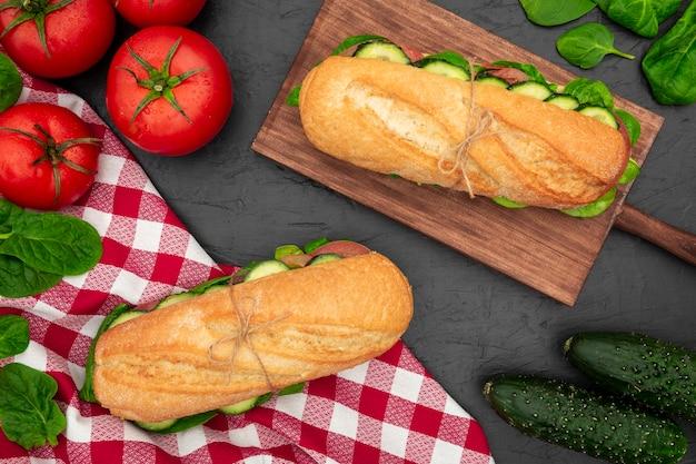 Mise à plat de tomates et concombres avec sandwichs et épinards