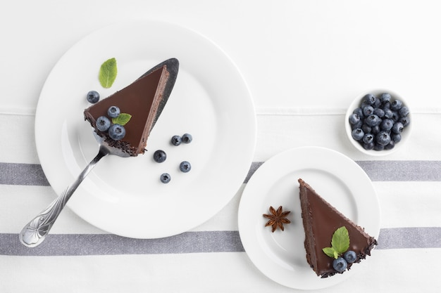 Mise à plat de tranches de gâteau au chocolat sur des assiettes avec des myrtilles