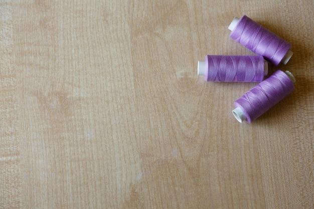 Mise à plat trois écheveaux de fil se trouvent sur une table en bois clair