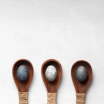 Mise à plat de trois œufs de pâques dans des cuillères en bois avec copie espace