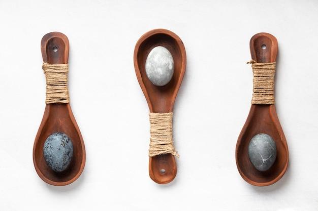 Mise à plat de trois œufs de pâques dans des cuillères en bois