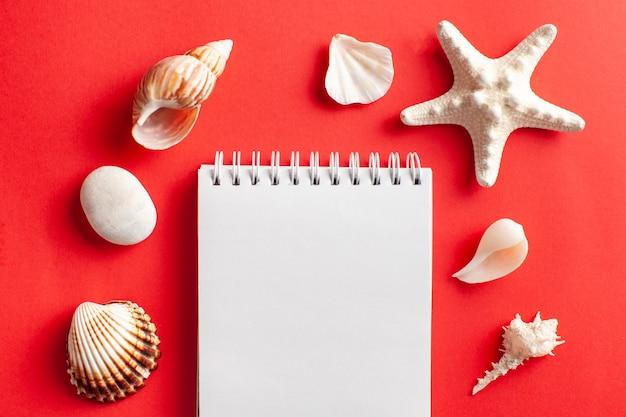 Mise à plat tropicale avec des coquilles d'étoiles de mer cahier vierge blanc sur rouge
