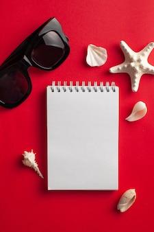 Mise à plat tropicale avec des coquilles d'étoiles de mer lunettes de soleil pour ordinateur portable blanc blanc sur rouge