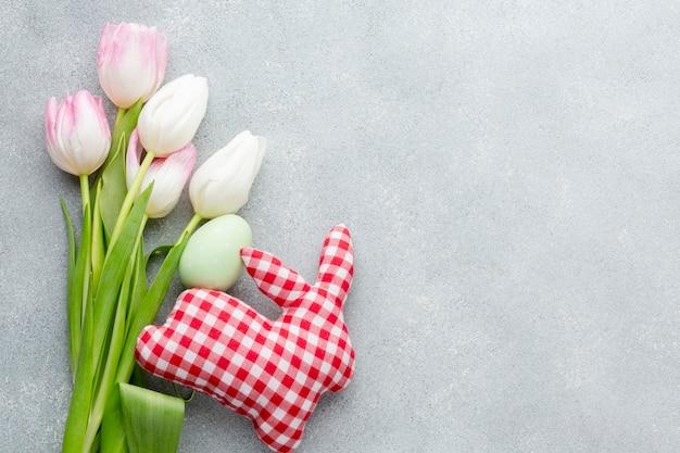 Mise à plat de tulipes colorées et oeuf de pâques avec décoration en forme de lapin
