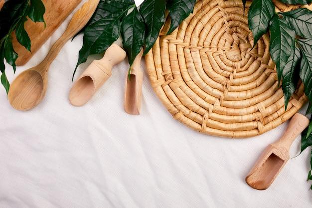 Mise à plat avec des ustensiles de cuisine en bois avec des feuilles vertes, des ustensiles de cuisine sur fond textile, collection de ktchenware capturée par le haut, maquette, cadre.
