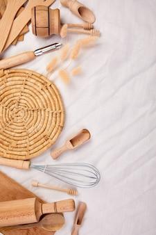 Mise à plat avec des ustensiles de cuisine en bois, des ustensiles de cuisine sur fond textile, collection de ktchenware capturée d'en haut, maquette, cadre.