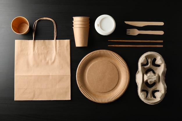 Mise à plat avec vaisselle écologique sur fond noir, vue de dessus