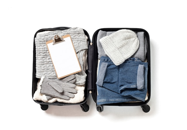 Mise à plat avec valise ouverte avec des vêtements décontractés pour l'automne, vacances d'hiver sur un mur blanc. vacances d'hiver, voyage, tourisme, concept de bagages de vol. vue de dessus