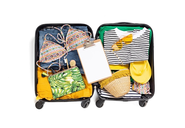 Mise à plat avec valise ouverte avec des vêtements décontractés pour les vacances d'été sur un mur blanc. vacances d'été, voyage, tourisme, concept de bagages de vol. vue de dessus