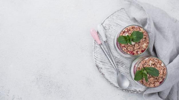 Mise à plat de verres de yaourt avec des céréales et de la menthe