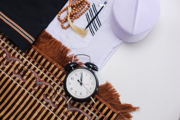 Mise à plat de vêtements musulmans et accessoires pour salat avec chapelet et horloge montrant l'heure de dhuhr prier