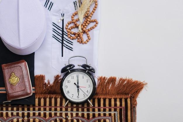 Mise à plat de vêtements musulmans et d'accessoires pour la salat avec le livre saint d'al coran et des perles de prière et une horloge indiquant l'heure du maghreb prient il y a un mot arabe qui signifie livre saint