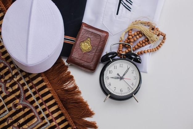 Mise à plat de vêtements musulmans et d'accessoires pour la salat avec le livre saint d'al coran et des perles de prière et une horloge indiquant l'heure de duha prier il y a un mot arabe qui signifie livre saint