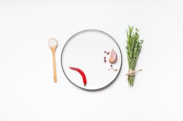 Mise à plat vue aérienne maquette plaque vide carte d'invitation espace texte vierge sur fond blanc avec des herbes vertes et des épices. fond de nourriture de conception de menu avec des ingrédients de cuisine