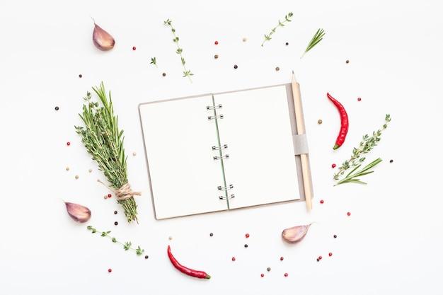 Mise à plat vue aérienne pages vierges pour ordinateur portable maquette espace texte carte d'invitation sur fond blanc avec des herbes vertes et des épices. conception d'un menu ou d'un livre de recettes ou d'un blog culinaire avec des ingrédients de cuisine
