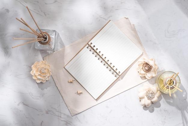 Mise à plat, vue de dessus d'un cahier ouvert avec une bouteille d'arôme en verre et des bâtons en bois sur la table
