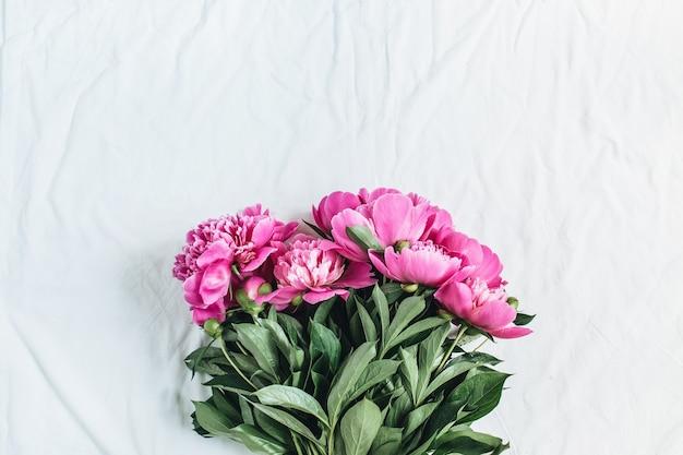 Mise à plat, vue de dessus du bouquet de fleurs de pivoines roses sur une surface de couverture blanche