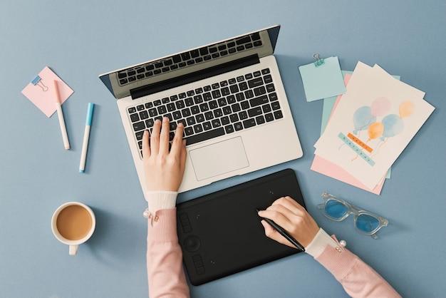 Mise à plat, vue de dessus du designer travaillant à son bureau