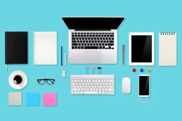Mise à plat ou vue de dessus espace de travail bureau vert avec ordinateur portable, fournitures de bureau, tablette, téléphone portable et tasse à café