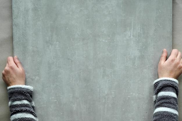 Mise à plat, vue de dessus avec des mains féminines en molleton gris rayé tenant une grande planche en pierre, copy-space