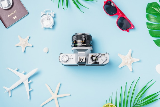 Mise à plat vue de dessus maquette caméra rétro films passeport avion coquilles d'étoiles de mer voyageur accessoires tropicaux sur un bleu avec copie espace vacances voyage d'été et concept de voyage d'affaires