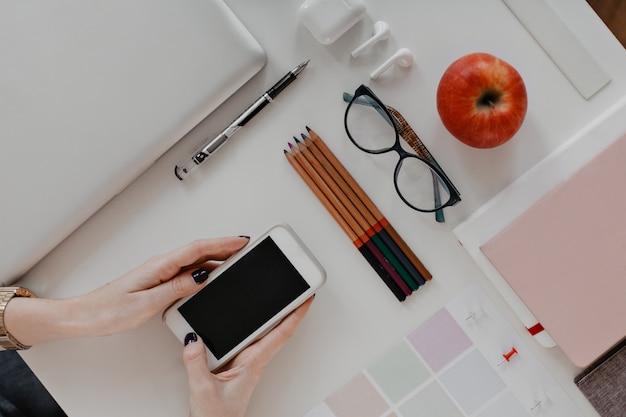 Mise à plat. womans mains tenant l'iphone sur des crayons, des lunettes, un ordinateur portable.
