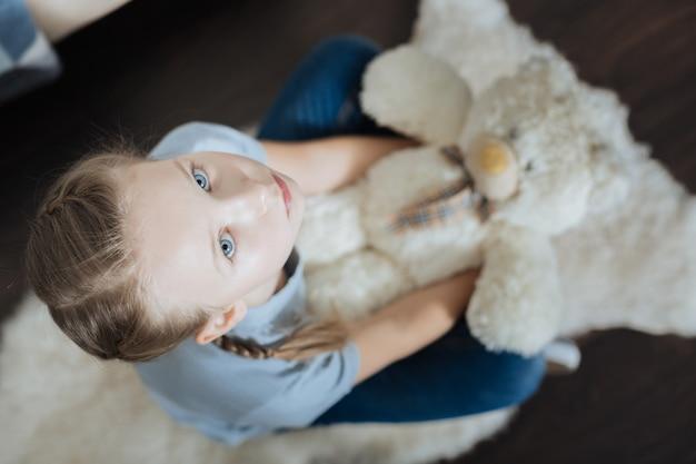 Misérable petite fille aux yeux bleus étreignant et tenant son ours en peluche alors qu'il était assis dans le fauteuil