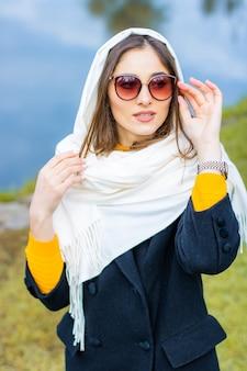 Miss habillée en manteau avec des lunettes près du lac