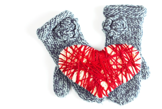 Mitaines bleues de femme ou de fille et carte de valentine de coeur rouge tissée sur un fond blanc d'isolement