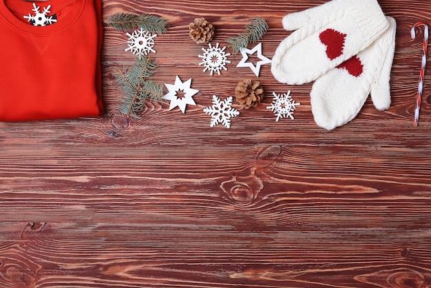 Mitaines de chandail rouge et décor de noël sur fond de bois