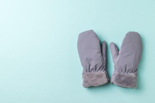 Mitaines grises isolées de fourrure sur fond bleu. accessoires pour la protection des mains.