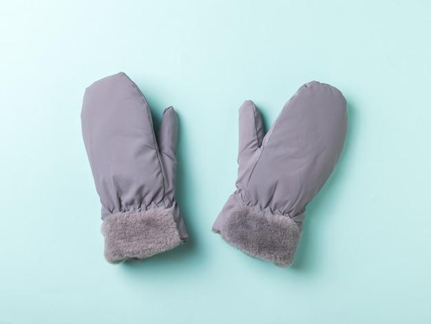 Mitaines pour femmes grises et chaudes sur une surface bleue. accessoires pour la protection des mains.