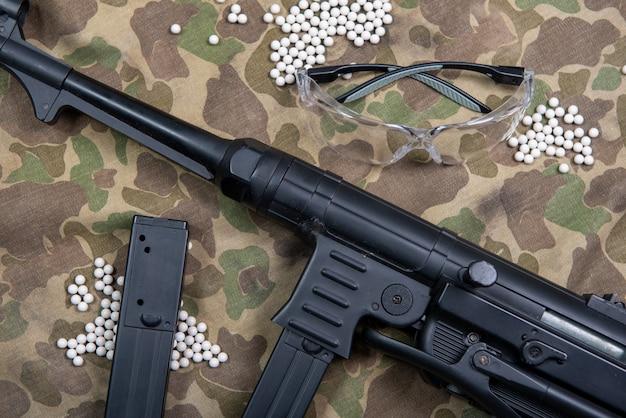 Mitrailleuse à air comprimé avec des lunettes de protection et beaucoup de balles