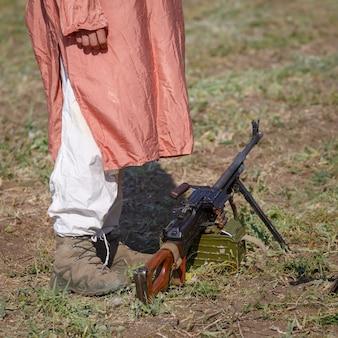 La mitrailleuse sur le terrain à côté d'un soldat debout dans des vêtements islamiques traditionnels
