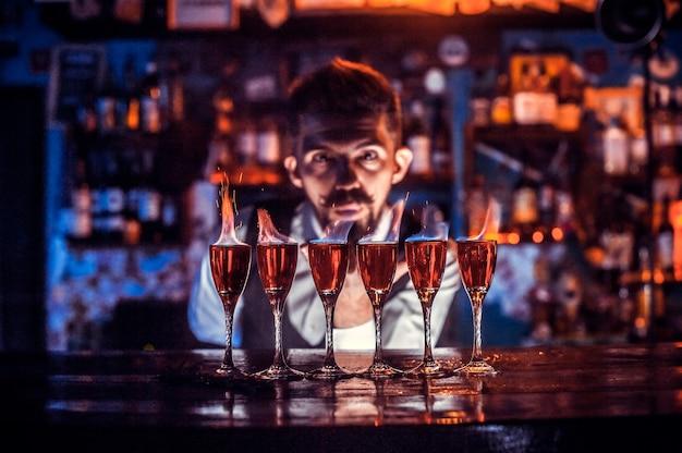 Un mixologue spécialisé montre le processus de préparation d'un cocktail dans les bars à cocktails