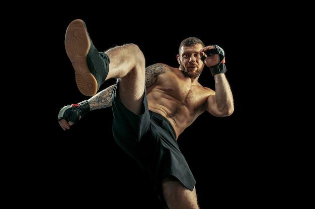Mma. boxe boxeur professionnel isolé sur fond de studio noir. ajustement des combats d'athlètes caucasiens musclés. concept de sport, de compétition, d'excitation et d'émotions humaines