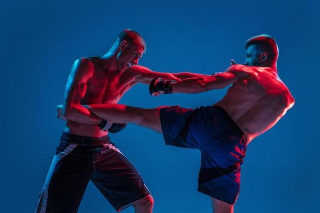 Mma. deux combattants professionnels poinçonnant ou boxant isolés sur fond bleu studio en néon. ajustez les athlètes ou les boxeurs caucasiens musclés qui se battent. sport, compétition et émotions humaines, annonce.