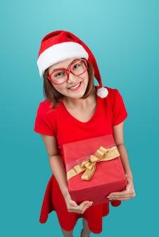 Mme santa. belle jeune femme asiatique au chapeau de père noël tenant un cadeau isolé sur bleu.